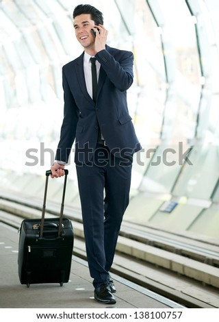 Portrait of a handsome businessman commuting to work and talking on mobile phone - stock photo