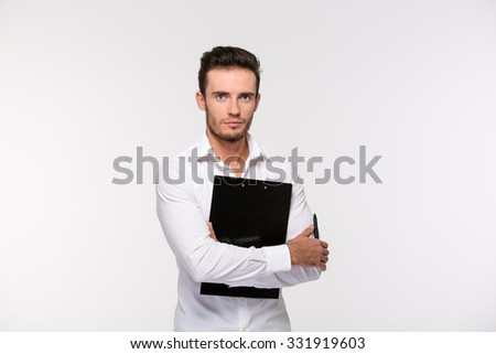 Portrait of a handsome businessman holding clipboard and looking at camera isolated on a white background - stock photo