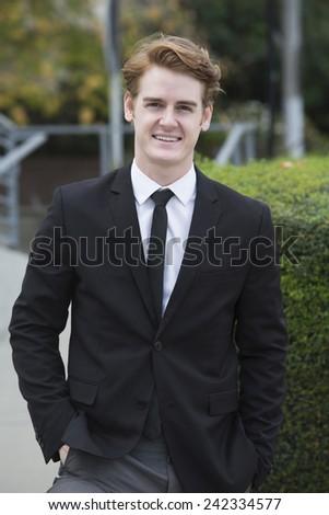 portrait of a handsome businessman in a black suit - stock photo