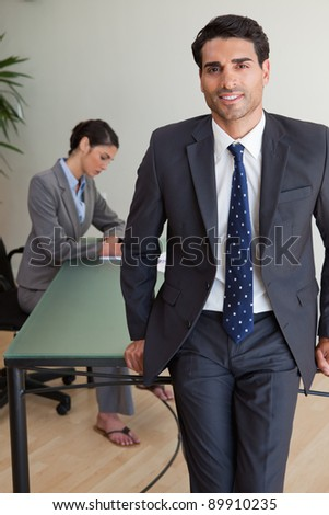 Portrait of a handsome businessman posing while his colleague is working in an office - stock photo