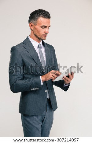 Portrait of a handsome businessman using tablet computer isolated on a white background - stock photo