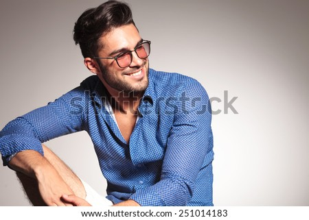 Portrait of a handsome fashion man smiling while looking away from the camera. - stock photo