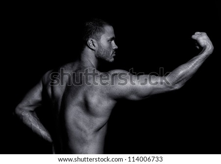 Portrait of a handsome guy showing his power. Black and white - stock photo