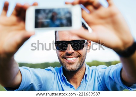 Portrait of a handsome happy man taking a selfie outdoors with his smartphone - stock photo