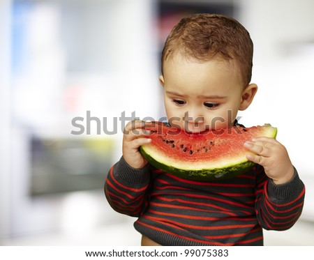 portrait of a handsome kid holding a watermelon piece - stock photo