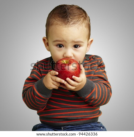 portrait of a handsome kid licking a red apple over grey background - stock photo