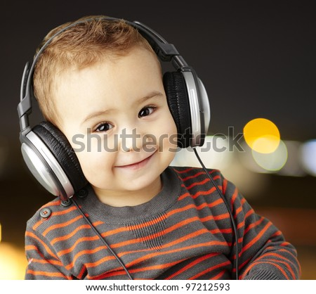 portrait of a handsome kid listening to music and smiling at a city night background - stock photo
