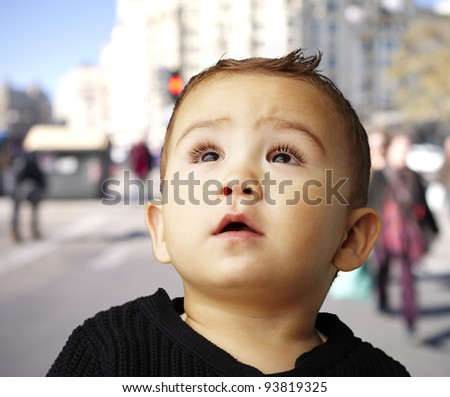 portrait of a handsome kid looking up against a crowded street - stock photo