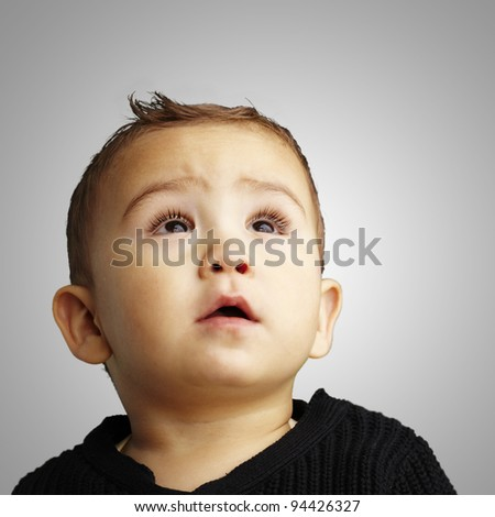 portrait of a handsome kid looking up against a grey background - stock photo