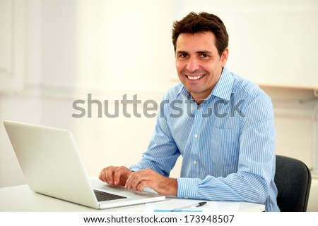 Portrait of a handsome latin businessman smiling at you while working on his laptop and sitting on office desk - copyspace - stock photo