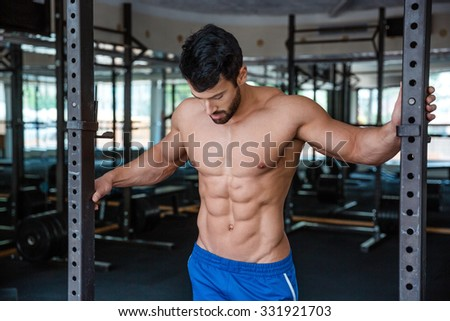 Portrait of a handsome male bodybuilder standing in fitness gym - stock photo