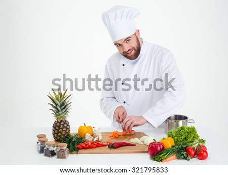 Portrait of a handsome male chef cook cutting vegetables isolated on a white background - stock photo