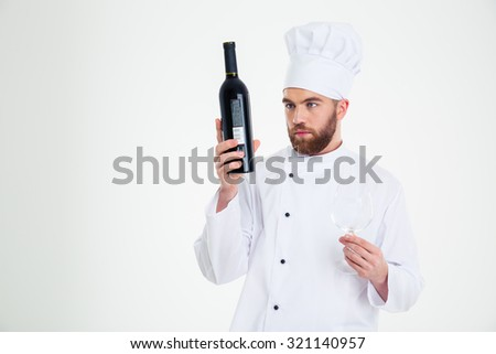 Portrait of a handsome male chef cook looking on bottle with wine isolated on a white background - stock photo