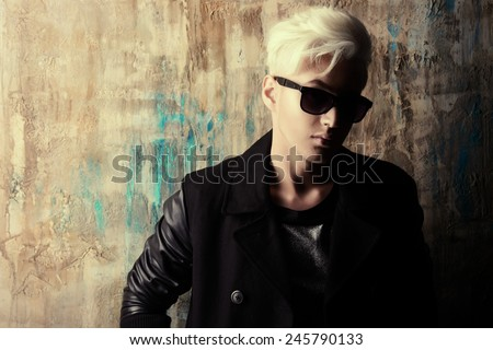 Portrait of a handsome male model with blond hair wearing black jacket and sunglasses. Urban style. Fashion. - stock photo