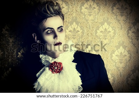 Portrait of a handsome male vampire over vintage background. Halloween. Dracula costume. - stock photo