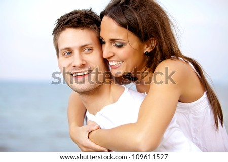 Portrait of a handsome man carrying his girlfriend on his back - stock photo