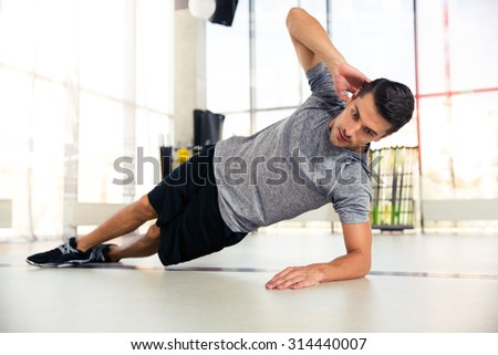 Portrait of a handsome man doing side plank at gym - stock photo