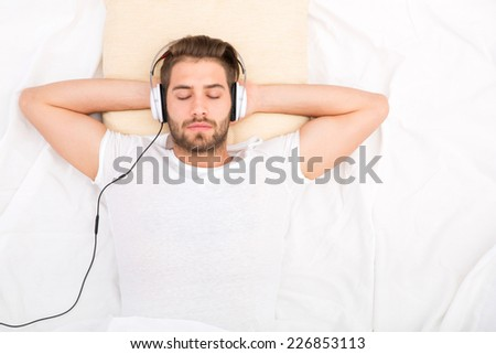 Portrait of a handsome man from above with headphones in bed.  - stock photo