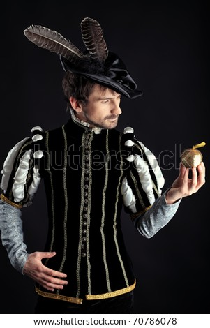 Portrait of a handsome man grandee in 16th century costume. Shot in a studio over black background. - stock photo