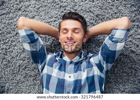 Portrait of a handsome man resting on the floor at home - stock photo