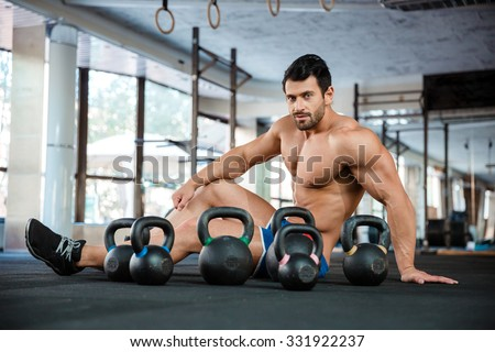 Portrait of a handsome man siting on the floor with kettle balls in fitness gym and looking at camera - stock photo