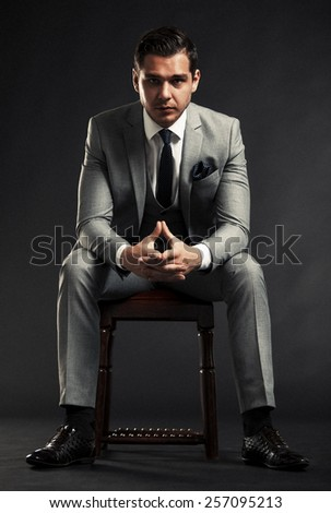 Portrait of a handsome man sitting in the armchair over black background - stock photo