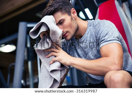 Portrait of a handsome man sitting on the bench with towel in fitness gym - stock photo