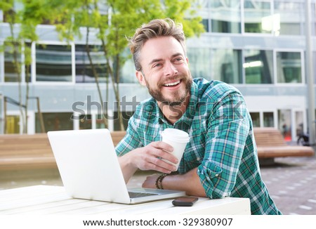 Portrait of a handsome man sitting outdoors with laptop and coffee - stock photo