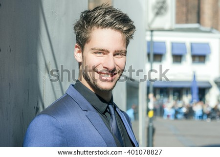 Portrait of a handsome man smiling and wearing a blue suit - Attractive male model - stock photo