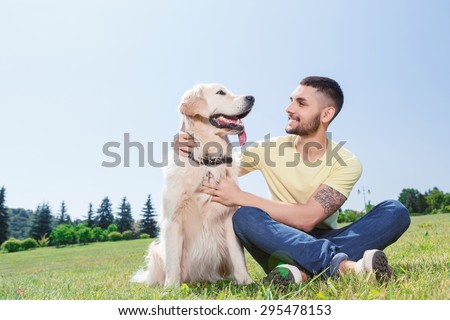 Portrait of a handsome man wearing yellow t-short and jeans with tattoo on his arm sitting on the grass, looking smiling on his lovely golden retriever in the park - stock photo