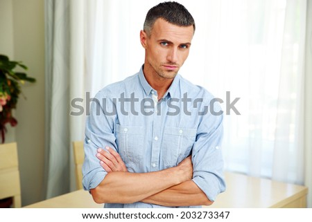 Portrait of a handsome man with arms folded at home - stock photo