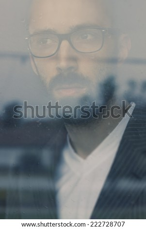Portrait of a handsome man with beard, wearing suit and glasses. Daydreaming and looking through the window - stock photo