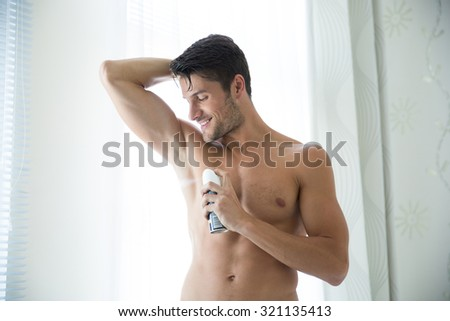 Portrait of a handsome man with deodorant at home - stock photo