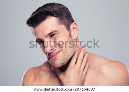 Portrait of a handsome man with neck pain over gray backgorund - stock photo