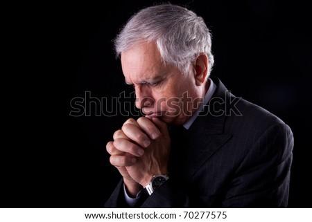 Portrait of a handsome mature businessman, thinking praying,  on black background, studio shot - stock photo