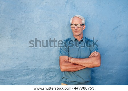 Portrait of a handsome mature man wearing glasses standing against blue background. Man with arms crossed looking away at copy space against blue wall. - stock photo