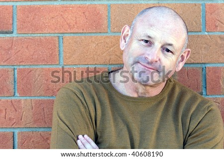 Portrait of a handsome middle aged man standing next to a brick wall with his hands folded - stock photo