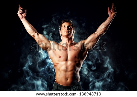 Portrait of a handsome muscular bodybuilder posing over black background. - stock photo