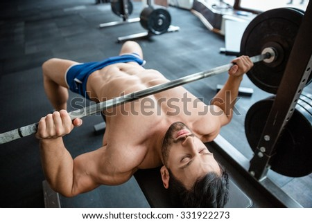 Portrait of a handsome muscular man doing bench press in fitness gym - stock photo