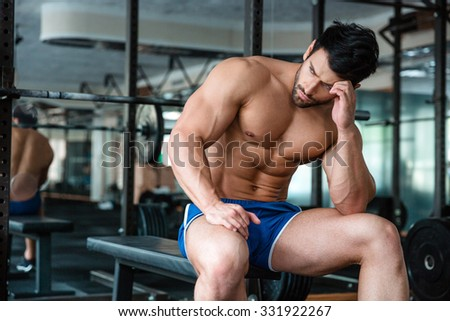 Portrait of a handsome muscular man resting on the bench in fitness gym - stock photo
