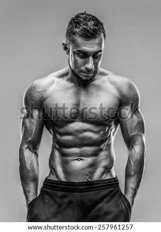 Portrait of a handsome muscular man standing over gray background. HDR monochrome. - stock photo