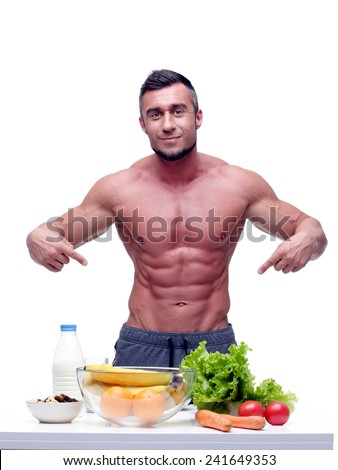 Portrait of a handsome muscular man with healthy food - stock photo