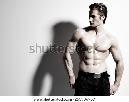 Portrait of a handsome muscular young man posing at studio as fashion model on a gray background with contrast shadows. - stock photo