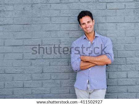 Portrait of a handsome older man smiling with arms crossed against gray background - stock photo