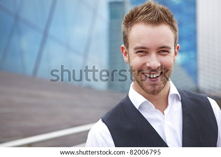 Portrait of a handsome smiling young business man. Outdoor photo. - stock photo