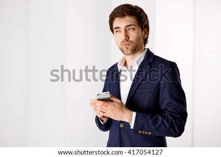 Portrait of a handsome smiling young businessman in suit holding money looking away. - stock photo