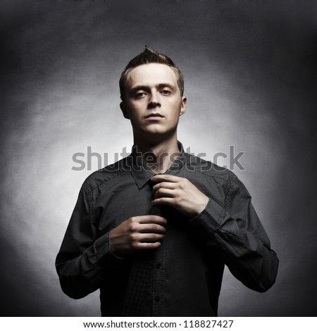Portrait of a handsome stylish young man tie a tie - stock photo