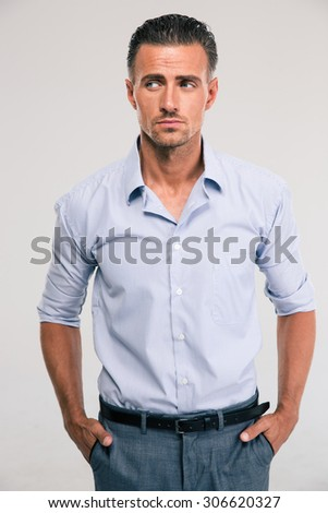 Portrait of a handsome thoughtful businessman looking away at copyspace over gray background - stock photo