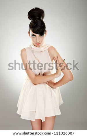 Portrait of a handsome woman model in white dress. She has a hand on her waist and the other on her opposite arm. - stock photo