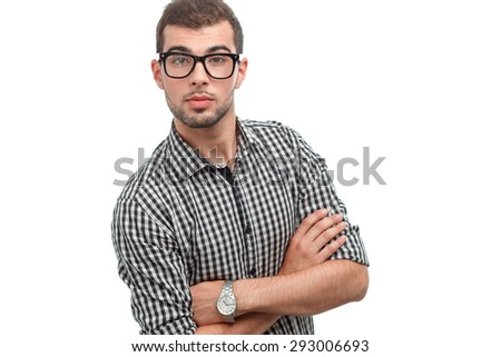 Portrait of a handsome young bearded man wearing a checkered shirt and glasses standing with arms crossed looking at the camera, isolated on white background - stock photo